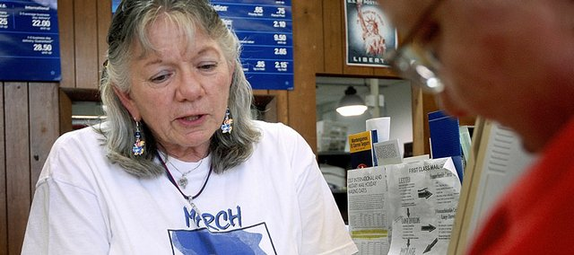 Diane Menzie, an employee at Lawrence's main post office, was among the Lawrence workers who couldn't watch KU play Thursday.