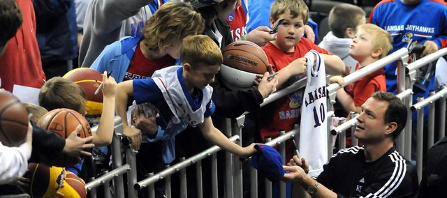 Jayhawk fans crowd against the railing to collect autographs from Kansas University basketball coach Bill Self following the team practice at the Qwest Center. The Jayhawks held a 32-minute practice Wednesday in Omaha, Neb., in preparation for today's NCAA Tournament opener at 11:25 a.m. against Portland State.