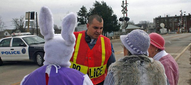 Jeannie Bandermann, dressed as the Easter Bunny; Ruth Muehler, right center; and Hilda Bandermann, right, are stopped by a police barricade Friday after attempting to visit friends as parts of downtown became submerged due to flooding from the Meramec River, in Pacific, Mo.