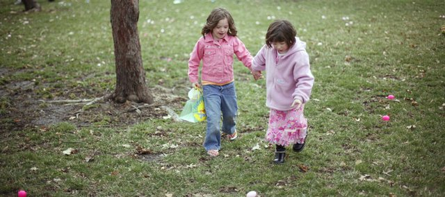Seven-year-old Bethany Barclay, left, and 5-year-old Amy Manning race around hand-in-hand to pick up eggs Saturday during the Egg Hunt Eggstravaganza at South Park. About 1,000 people showed up for the hunt.