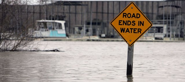 A descriptive sign stands as water rises Saturday in New Athens, Ill. Much of the flooding in Illinois was in sparsely populated areas, but several dozen people were evacuated from their homes in Murphysboro on Saturday, said Patti Thompson, a spokeswoman for the Illinois Emergency Management Agency.