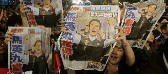 "Supporters of Taiwan's opposition Nationalist Party presidential candidate Ma Ying-jeou raise newspaper headline that reads ""Ma Ying-jeou elected"" as they celebrate Ma's victory in the presidential election Saturday in Taipei, Taiwan."