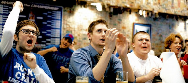 "From left, KU seniors Corey O'Neal, of Leawood, Kyle Klem, of Denver, and David Ehret, of Topeka, cheer for the Kansas University Jayhawks on Saturday at Jefferson's Restaurant, 743 Mass. Klem said he filled out a bracket, but it isn't faring well. ""Now I'm rooting for upsets in KU's bracket so we play easy teams,"" he said."