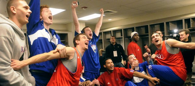 The Kansas Jayhawks go wild as they watch the dramatic overtime finish of the Western Kentucky win over Drake on a TV set March 21 in their locker room at the Qwest Center in Omaha, Neb. Journal-World photographer Nick Krug waited for about 50 members of the media to leave the locker room before he could capture this spontaneous team moment.
