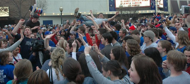 Hundreds of Kansas University fans filled Massachusetts Street on Sunday, with one even enjoying a little body-surfing, after KU advanced to its first Final Four since 2003 in the NCAA basketball tournament. The Jayhawks defeated Davidson 59-57 Sunday in thrilling fashion and will face North Carolina and former KU coach Roy Williams on Saturday in San Antonio.