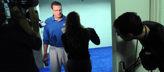 A journalist peeks around the corner as Kansas coach Bill Self is interviewed by a TV crew. Self today will seek his first trip to the Final Four.