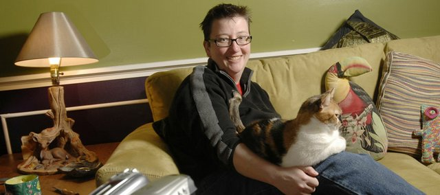 "Through a grant, Tami Albin, Lawrence, has created a gay, lesbian, bisexual, transgender, intersex and queer oral history collection titled ""Under the Rainbow: Oral Histories of GLBTIQ People in Kansas."" Albin was photographed in her Lawrence home with her cat Maggie."