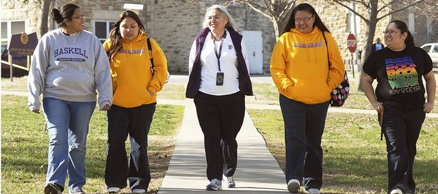 Haskell Indian Nations University president Linda Warner, center, walks Wednesday on campus with students, from left, Recinda Adams, Albuquerque, N.M., senior; Tashina Tahdooahnippah, Lawrence junior; Rebecca Jamison, White Swan, Wash.; and MayAnne Mitchell, Warm Springs, Ore. Warner been the president for one year.