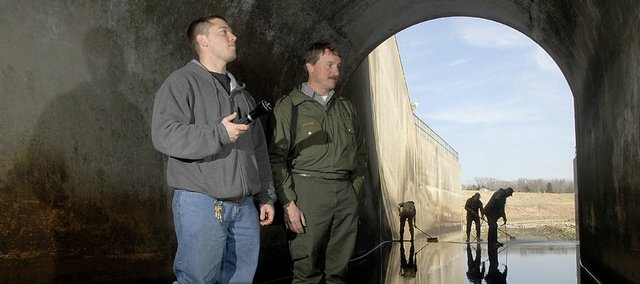 Brian Turk, left, a civil engineering technician for the U.S. Corps of Engineers, and Kipp Walters, a park ranger with the corps at Clinton Lake, inspect tunnel walls inside the dam at Clinton. A comprehensive five-year inspection of the dam was done this week.