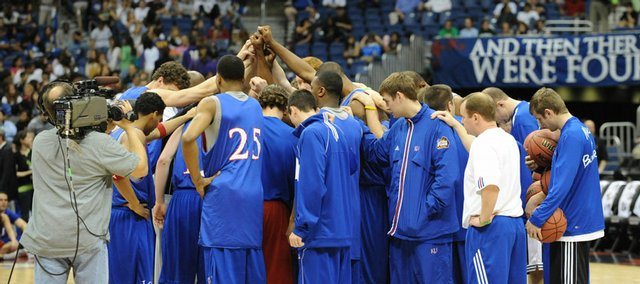 The Kansas Jayhawks huddle at center court before practice Friday at the Alamodome in San Antonio. KU meets North Carolina at 7:47 tonight in the Final Four of the NCAA Basketball Tournament. Watch it on CBS, Sunflower Broadband channels 5, 13, 201.