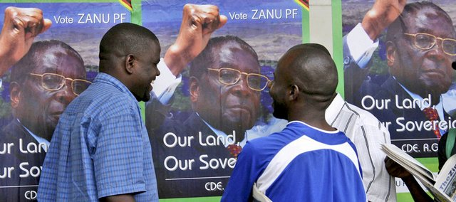 Men talk in front of posters of the leader of Zimbabwe African National Union-Patriotic Front, Zimbabwean incumbent President Robert Mugabe, on Thursday in Harare, Zimbabwe.