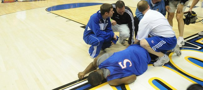 Kansas guard Rodrick Stewart (5) pounds his fist on the ground as coach Bill Self and trainers tend to Stewart's right knee. Stewart fractured his right kneecap during a dunk drill, ending his season.