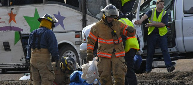 Emergency workers examine the scene of a bus crash Saturday in Albertville, Minn. A bus carrying students and their chaperones home from a band trip to Chicago rolled over on a highway Saturday, killing one student and injuring the dozens of others on board, authorities said.