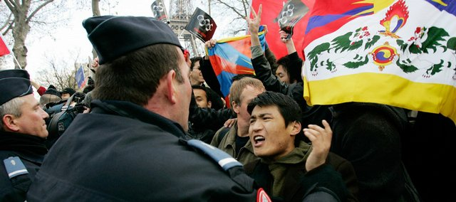 Police officers detain an anti-China, pro-Tibet demonstrator waving a Tibetan flag during the Olympic torch relay shortly after its beginning Monday near the Eiffel Tower in Paris. Chaotic protests against China's human- rights policies forced security officials to extinguish the Olympic torch several times during the relay.