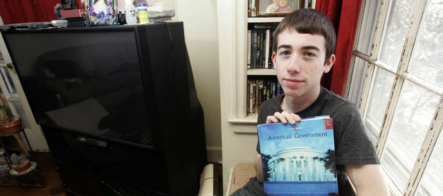 Matthew LaClair, 18, holds his American Government textbook at his home Tuesday in Kearny, N.J. LaClair, a senior at Kearny High School, has raised questions about political bias in a popular textbook on U.S. government, and legal scholars and top scientists agree.