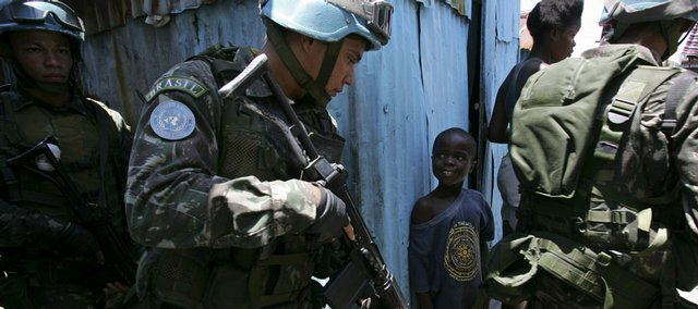 UN peacekeepers pass a boy during a foot patrol Friday at the Cite Soleil slum in Port-au-Prince. Protesters abandoned roadblocks and businesses reopened in Haiti's debris-littered capital, but some warned that chaos will quickly return if the government does not rein in soaring food prices.
