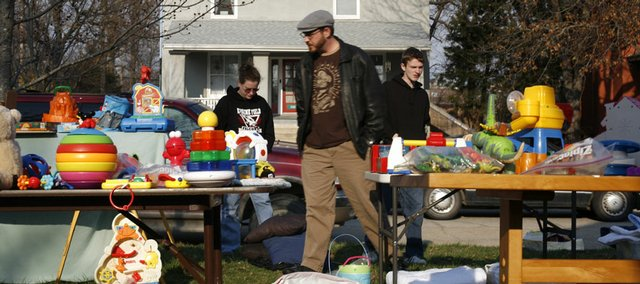 April Helphrey, left, and Randy Helphrey, both of Lawrence, and Josh Love, of Ottawa, browse through goods at an April 5 sale at 1424 N.Y. Books, shoes, toys and baby clothing tend to sell better at yard sales than online services, says veteran garage saler Colleen Edwards of Fresno, Calif.