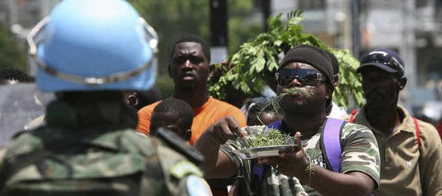 A demonstrator eats grass in front of a U.N. Brazilian peacekeeping soldier during a protest last week against the high cost of living in Port-au-Prince, Haiti. Some aid organizations in the country are warning of a widening nutritional crisis in Haiti, where spiraling food prices have sparked more than a week of violent protests.