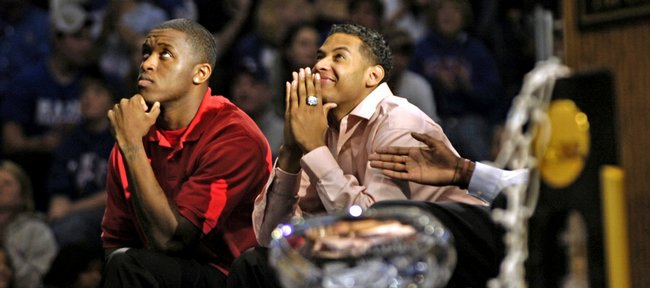 Seniors Rodrick Stewart, left, and Jeremy Case watch a highlight reel during the KU basketball awards ceremony at Allen Fieldhouse.