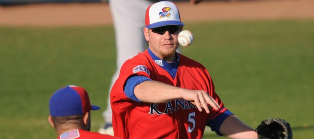 KU third baseman Matt Berner throws to first around pitcher Hiarali Garcia. Kansas defeated Baker, 11-6, Tuesday at Hoglund Ballpark.