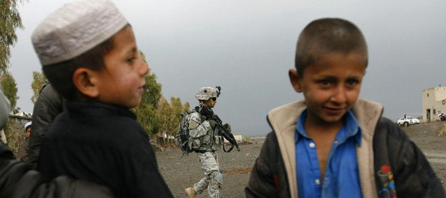 A U.S. soldier of the 101st Airborne Division is seen during a patrol, as Afghan boys look on in Khost, Afghanistan. U.S. troop levels in Afghanistan now top 32,000, the highest number of American forces in the country since the 2001 U.S.-led invasion that toppled the Taliban. U.S. military officials would like to see the NATO-led force grow by several thousand more troops, but American resources are stretched too thin and no other country is stepping up.