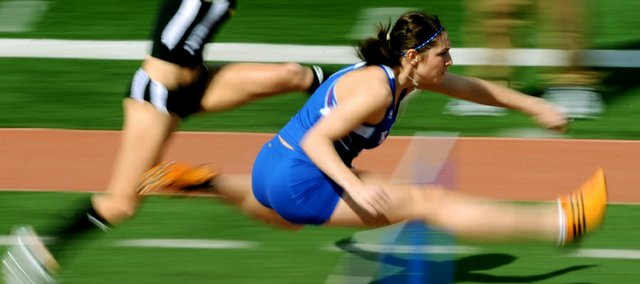 Kansas University heptathlete Chelsea Helm, right, clears an obstacle in the 100-meter hurdle event. Helm is in 12th place after Day One of the Kansas Relays on Wednesday at Memorial Stadium.