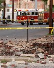 An emergency vehicle waits at the scene where rubble from earthquake damage lies strewn along a sidewalk in an old section of Louisville, Ky., Friday, April 18, 2008. The 5.2 magnitude earthquake, centered in southern Illinois, rattled skyscrapers in Chicago's Loop and homes in Cincinnati but appeared to cause no major injuries or damage.