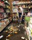 Mike Dunkel cleans up damaged stock in his Mt. Carmel, Ill., liquor store Friday after an early-morning earthquake struck. Some reported feeling the quake in Kansas.