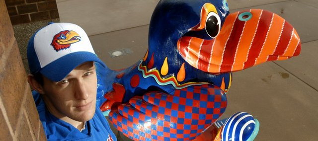 Kansas University senior Rick Phillips is making it his mission to get his photograph taken with as many Jayhawk statues from the Jayhawks on Parade as possible. Phillips is photographed by Mardis Gras on the Kaw Hawk by Janet Perkins, in front of the Lied Center on KU's West Campus.