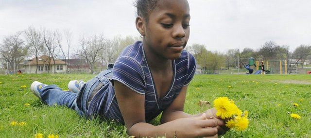 Ahbriana Garrett, 8, a student at Pinckney School, enjoys picking dandelions Monday in the schoolyard.
