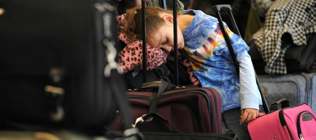 Trinity Maughan, 6, of Peoria, Ill., rests on a bag while waiting in line at O'Hare International Airport in Chicago in this April 9 file photo. For travelers, a vacation season of jammed planes, delayed flights and higher fares looms.