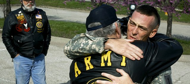 US Army Sgt. Joe Peel, right, of Tonganoxie, is greeted by his father, Eddy Peel, and other Patriot Guard Riders Friday during a stop in Lawrence. Peel returned to Kansas on Monday after serving a tour in Iraq. The Patriot Guard surprised him Friday with a motorcycle escort from Lawrence to Tonganoxie.