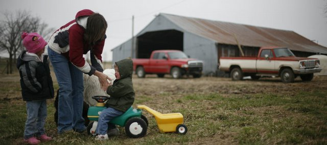 Josie Flory warms up the hands of her daughter Maris, 2, at right, while the family performs chores.