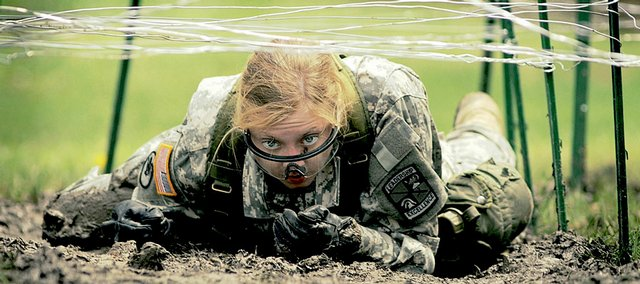 KU ROTC cadet Helen Draffen drags herself through the mud during an obstacle course competition Saturday at Clinton Outlet Park. Army ROTC cadets from across the country, representing 90 teams, participated in the KU Army ROTC Ranger Buddy Competition. The teams competed in several events, including a 5-kilometer buddy run, a knot-tying competition and the obstacle course.