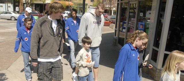 Students from New York School were paired Monday with athletes from Kansas University for LPS On the Move, a program to promote the importance of physical activity. Fourth-grader Kai Blosser, 10, center, was among the students joining KU men's basketball players Conner Teahan, left, and Cole Aldrich for a short stroll from the school at 936 N.Y. to Massachusetts Street.