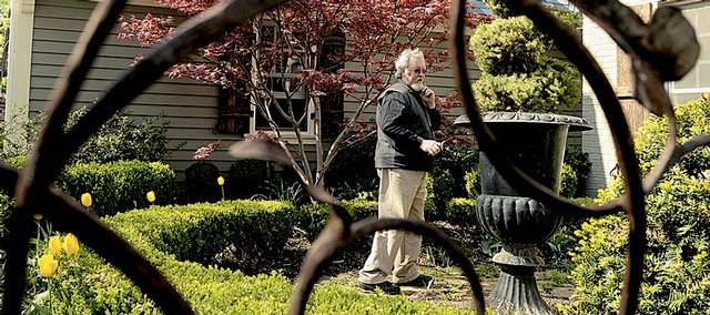 John McCaffrey, Lawrence, surveys the home of Eric and Megan Edwards on the 400 block of Lawrence Avenue. McCaffrey, who performs landscaping for several Lawrence clients, has used a colorful array of annuals to brighten up the property.