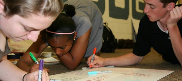 During their last PIECE session Wednesday, Kirstyn Heine, 15, Rachael Hodison, 15, and Reed Grabill, 15, summarize their thoughts on a PIECE poster.
