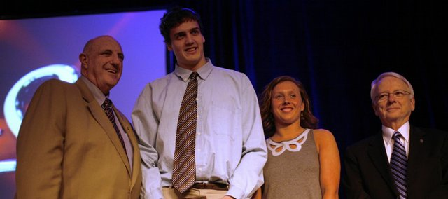 Kansas University seniors Sasha Kaun, second to left, and Terri Schramka, right, accept the Senior Scholar-Athlete awards. At left is athletic director Lew Perkins.
