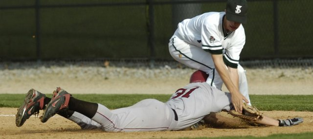 Free State's Tyler Hatesohl, top, tags a baserunner. The Firebirds drubbed Shawnee Mission North, 16-0, before lightning forced the game to be halted Thursday at FSHS.