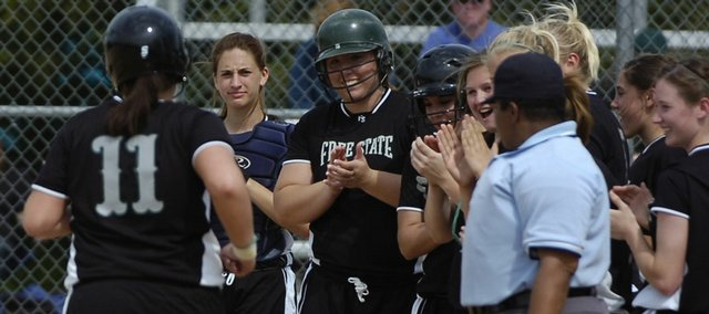 Teammates welcome Kayley Lane after her two-run home run. Free State splits its softball doubleheader Thursday at FSHS.