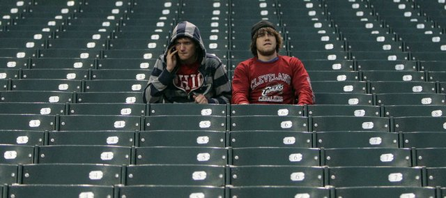 Two fans sit in their seats after the Kansas City Royals-Cleveland Indians baseball game was postponed due to the weather. The game was supposed to be played Friday in Cleveland.