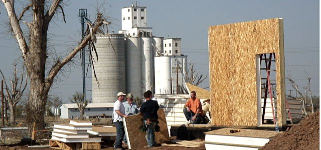 "Construction crews erect the first wall of a sustainable and energy-efficient home in front of the Greensburg grain elevator. Residents in Greensburg are slowly rebuilding their homes, many using ""green"" building approaches."
