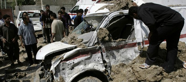 A man examines an ambulance destroyed in an apparent U.S. airstrike Saturday in the Shiite stronghold of Sadr City in Baghdad. The strike wounded nearly two dozen people.