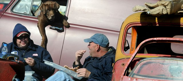 Interested in either the conversation or the leftover steak, Hoosier, a chocolate Lab hangs out of the window of a '57 Chevrolet truck near brothers Bobby Baker, left, and Rodney Baker, both of Houston, during the Antique Auto Club 2008 Swap Meet on Saturday at the Douglas County 4-H Fairgrounds. Vendors and car enthusiasts converged on Lawrence for the event to buy, sell and trade cars, car parts and other items.