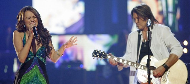 "Miley Cyrus and her father, Billy Ray Cyrus, sing a duet, ""Ready, Set, Go"" during the CMT Music Awards last month in Nashville. A risque photo of the teen idol in Vanity Fair has drawn her unwanted attention."