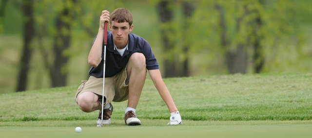 Seabury Academy freshman Reed Grabill studies a putt on the third hole. Grabill shot a 46 on the front nine to win Monday's matchup against KC Lutheran at Alvamar Country Club.