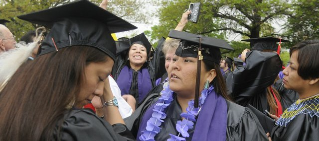 Felicia Francis, left, gets some help with her cap from Natasha Jake on Friday before heading into the Coffin Complex for graduation ceremonies.
