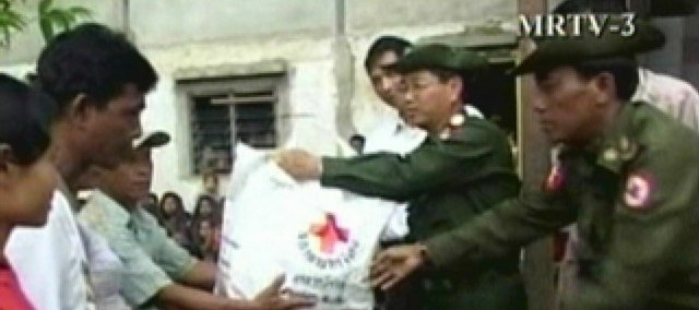 In this photo captured from video and released by the state television station MRTV-3, an unidentified military official passes out food aid at a relief camp Saturday in Myanmar. Myanmar's military regime distributed international aid Saturday but plastered the boxes with the names of top generals in an apparent effort to turn the relief effort for last week's devastating cyclone into a propaganda exercise.