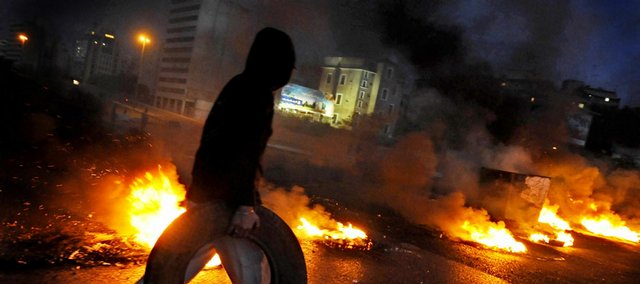 A Lebanese opposition supporter puts an additional tire onto a burning roadblock on Saturday in downtown Beirut, Lebanon. Hezbollah said Saturday it was withdrawing its gunmen from Beirut neighborhoods seized in sectarian clashes after the army ordered its troops to establish security and called on fighters to clear the streets.