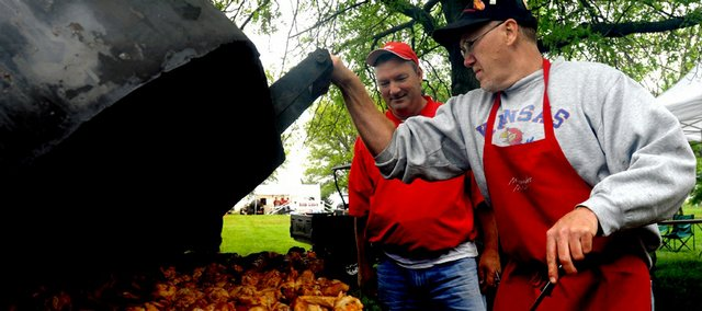 Lawrence resident and barbecue enthusiast Murray Renick pulls a smoked sausage out for Sertoma Club member Tom Pollard, Lawrence, as he oversees a grill full of buffalo wings for the 2008 Barbecue Cook-Off by the Lawrence Sertoma Club at Broken Arrow Park.
